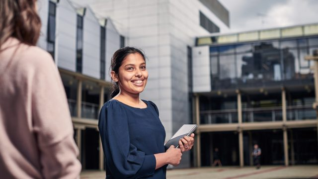 Student holding tablet and smiling as she walks through courtyard at Waterfront Campus