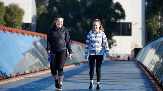 Two students walking across footbridge at Burwood Campus