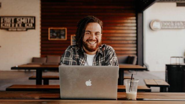 Man smiling as he sits at his laptop