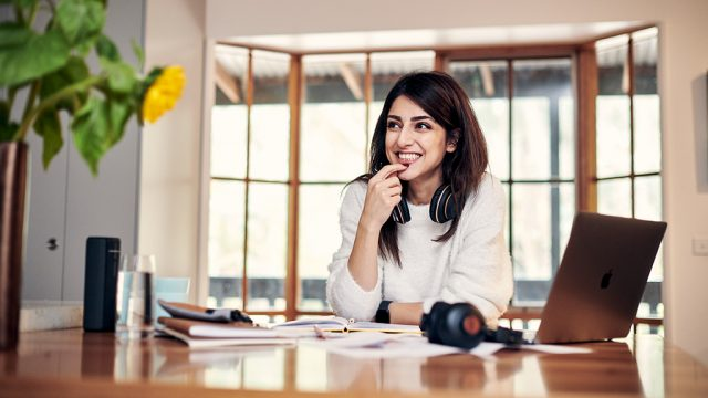 Smiling female student studying at home