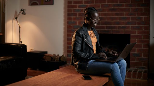 Smiling female international student at home with laptop