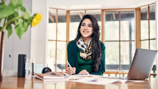 Student smiling as she writes in notebook while studying at home