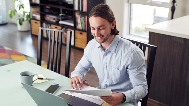 Student reading papers while seated at laptop at home