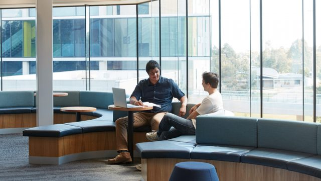 Two students chatting in a communal area at Burwood Campus