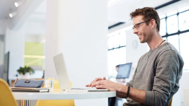 Student smiling as he works on laptop in office