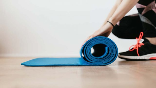 Woman unrolling exercise mat