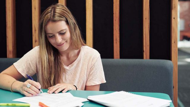 Student smiling as she studies in study hub at Burwood Campus