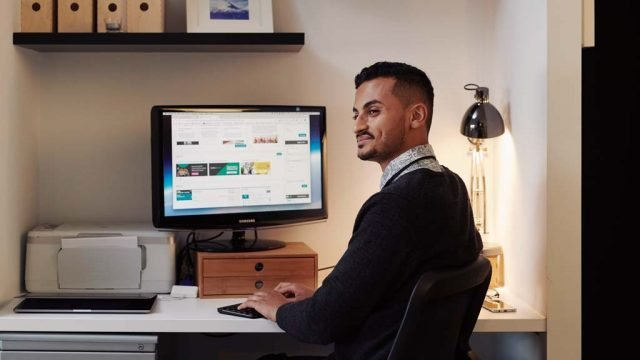 Student smiling as he looks away from computer while studying at home