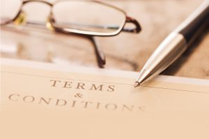 A terms and conditions contract with pen and glasses
