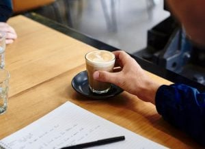 Student prepares to drink a coffee while working