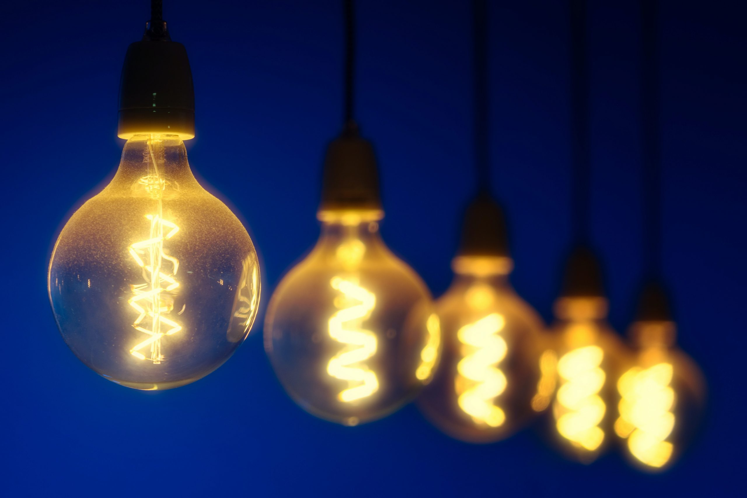 Receding row of lit yellow lightbulbs against a dark blue background