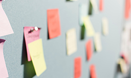 Out-of-focus photograph of assorted colourful post-it notes pinned to a grey background